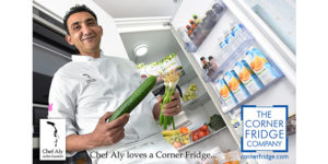 Chef Aly holding a cucumber and celery with an open cold room behind him