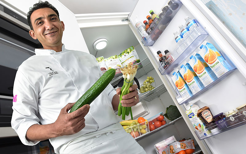 Chef Aly stands in front of his Corner Fridge